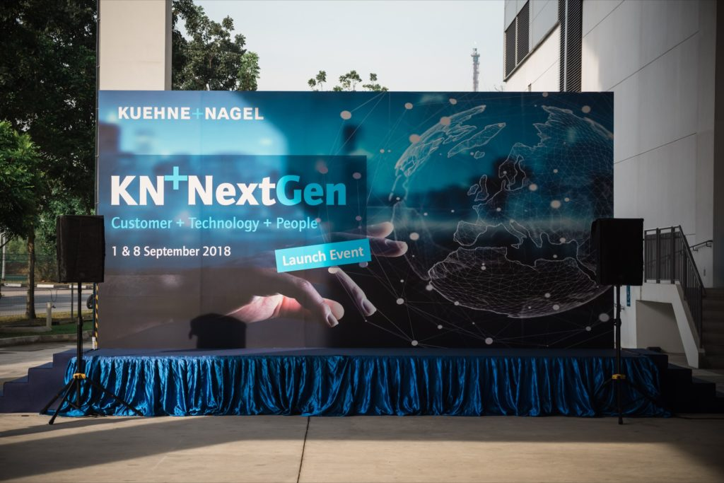 icube events_kuehne nagel next gen launch event external venue stage backdrop with mic and speakers